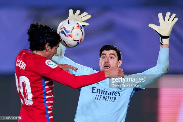 Thibaut Courtois of Real Madrid battles for the ball with Jesus Vallejo of Granada CF during the La Liga Santander match between Real Madrid and...