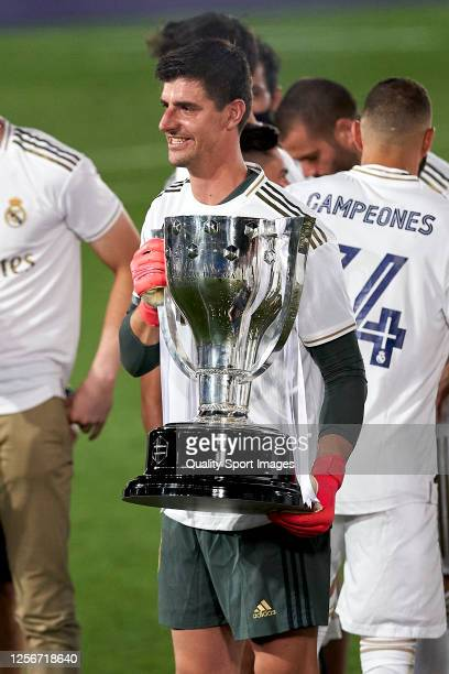 Thibaut Courtois of Real Madrid CF poses with the La Liga trophy after Real Madrid secure the La Liga title during the La Liga match between Real...