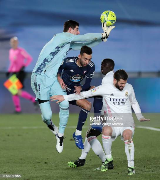 Thibaut Courtois of Real Madrid clears the ball ahead of Brais Mendez of Celta Vigo during the La Liga Santander match between Real Madrid and RC...