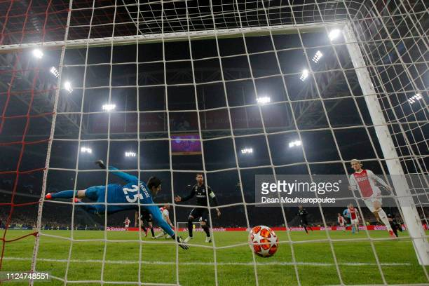 Thibaut Courtois of Real Madrid dives to save a shot from Hakim Ziyech of Ajax but fails and Ajax score there first goal during the UEFA Champions...