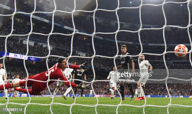 Thibaut Courtois of Real Madrid fails to stop Hakim Ziyech of Ajax from scoring his team's first goal during the UEFA Champions League Round of 16...