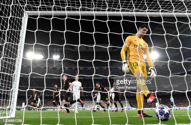 Thibaut Courtois of Real Madrid gathers the ball from the back of the net as Kevin De Bruyne of Manchester City celebrates after scoring a penalty...