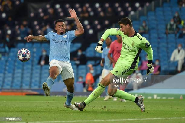 Thibaut Courtois of Real Madrid is challenged by Gabriel Jesus of Manchester City during the UEFA Champions League round of 16 second leg match...