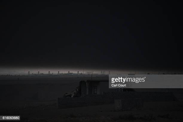 Thick black cloud hovers over buildings in the desert as an oil field that was set on fire by retreating ISIS fighters ahead of the Mosul offensive...