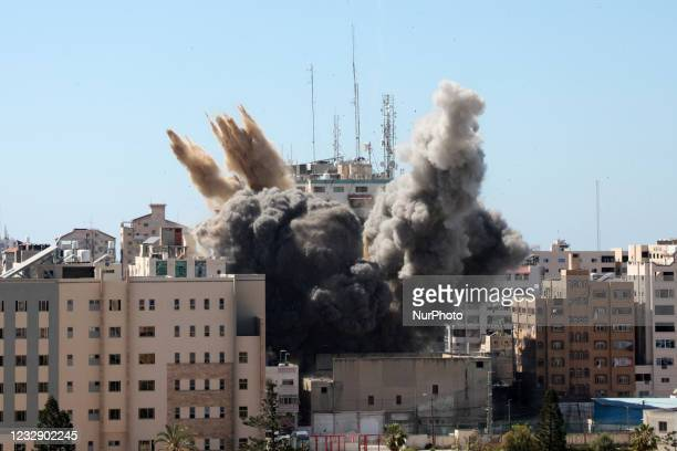 Thick column of smoke rises from the Jala Tower as it is destroyed in an Israeli airstrike in Gaza city controlled by the Palestinian Hamas movement,...