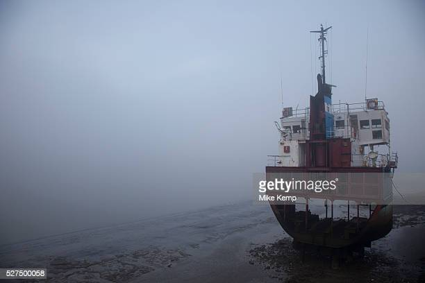 Thick fog obscures an old section of a large ship which sits in the muddy banks at low tide in London making a peaceful yet eerie landscape...