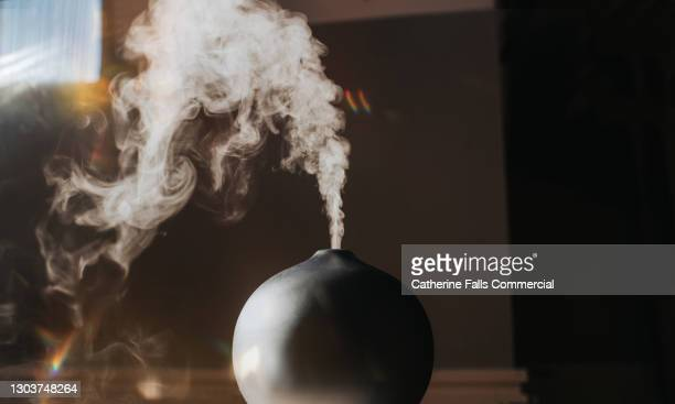 a thick mist gently rises and falls from an oil diffuser in a home environment - aromatherapy oil stock pictures, royalty-free photos & images