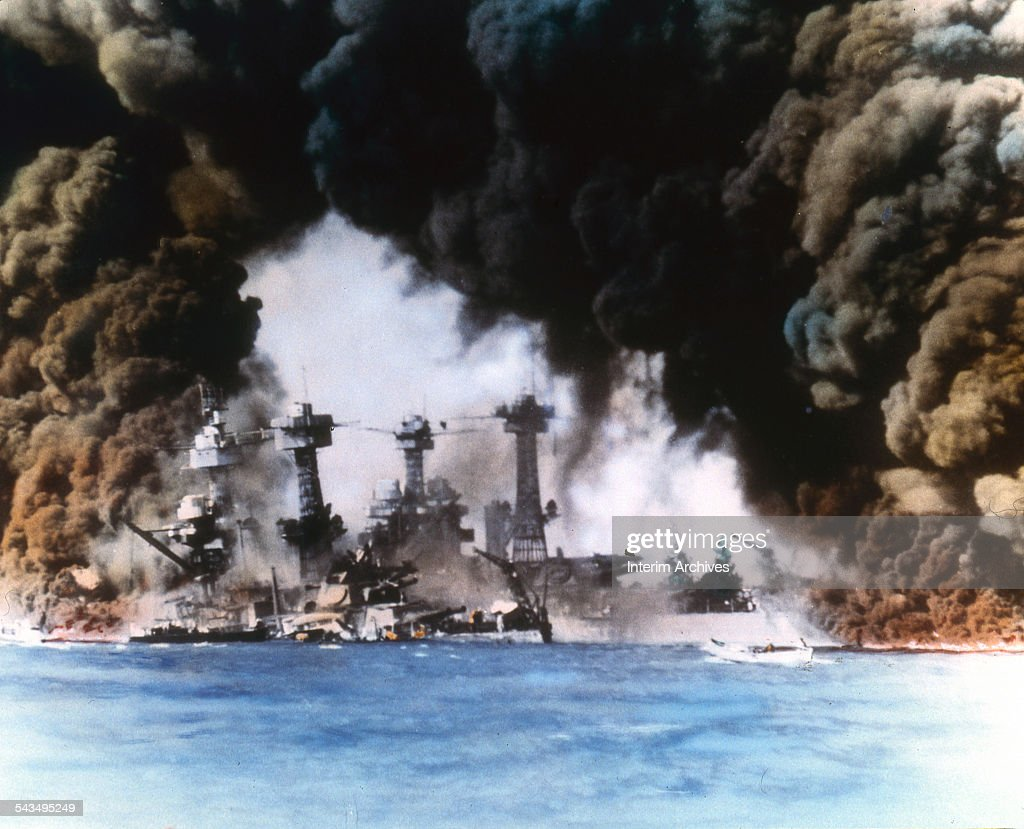 Thick smoke billows up from stricken American warships (from left, USS West Virginia and USS Tennessee) along battleship row during the Japanese attack on Pearl Harbor, Honolulu, Oahu, Hawaii, December 7, 1941.