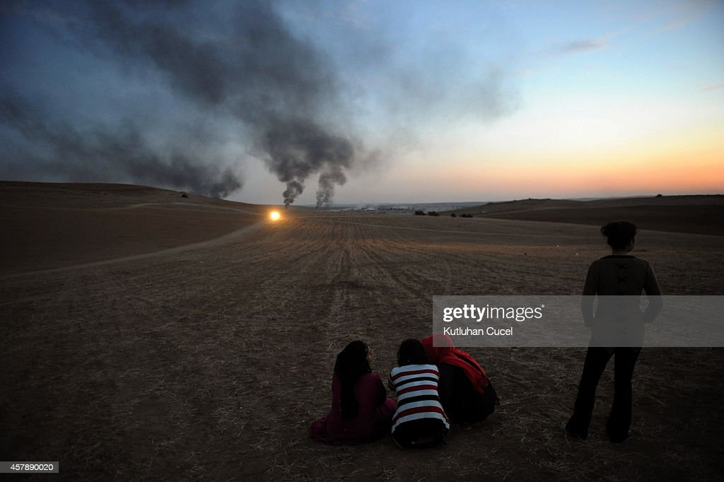 Thick smoke raises from the Syrian town of Kobani as a people watch the fighting between Islamic State militants and Kurdish People's Protection Unit (YPG) forces, as seen from the Mursitpinar crossing on the Turkish-Syrian border in Sanliurfa province October October 26, 2014. The Syrian town of Kobani has yet again seen fierce fighting between Islamic State and Syrian Kurdish forces. Since mid-September, more than 200,000 people from Kobani have fled into Turkey.