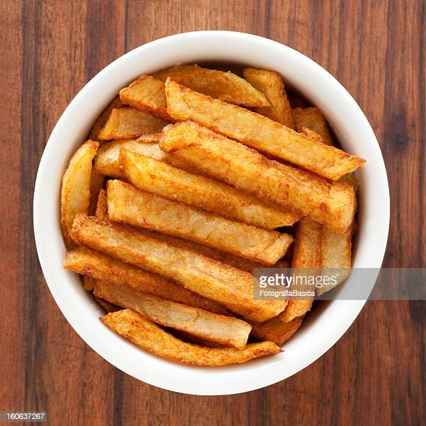 Thick-cut potato fries in a bowl on wood grain
