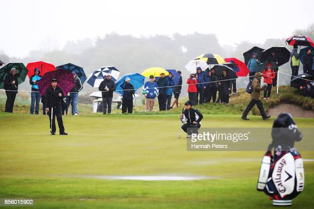 Thidapa Suwannapura of Thailand and Jing Yan of China wait for officials to look at the rain on the 2nd green during day four of the New Zealand...