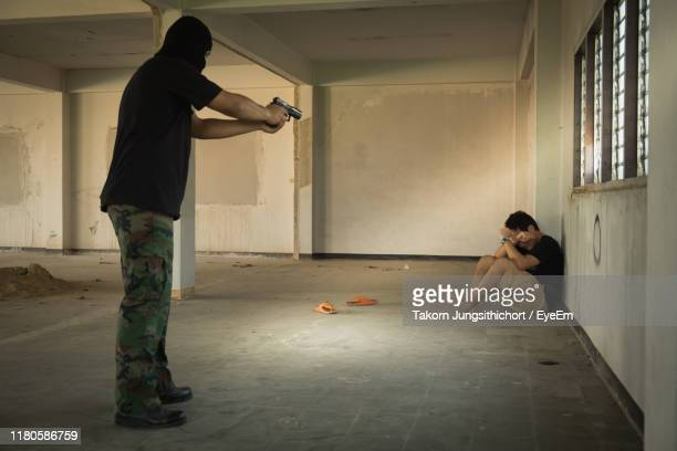 thief aiming handgun at man in building - gun stock pictures, royalty-free photos & images