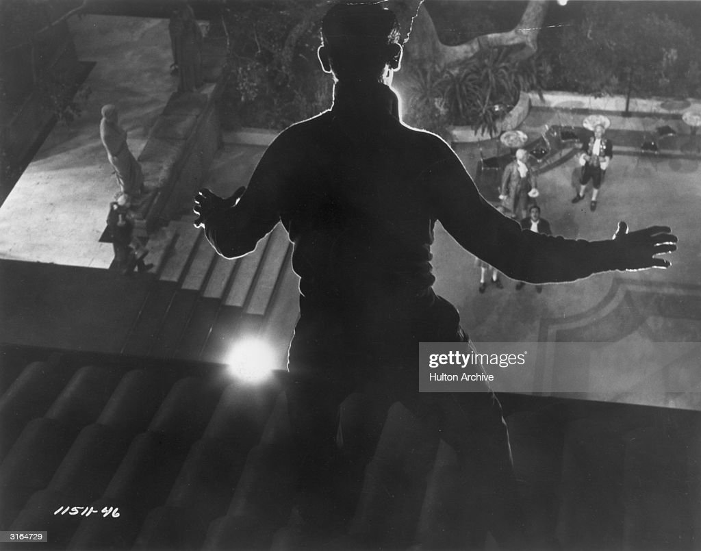 Thief Cary Grant (1904 - 1986) stands frozen in the light as he is spied on the roof in a scene from Hitchcock's film 'To Catch A Thief'.
