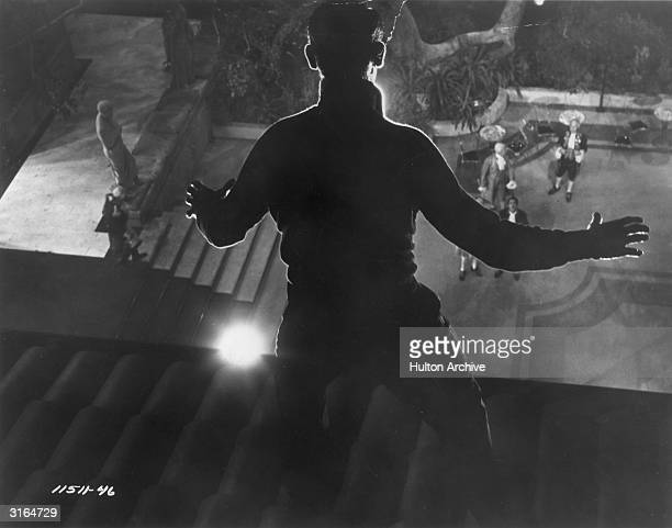 Thief Cary Grant stands frozen in the light as he is spied on the roof in a scene from Hitchcock's film 'To Catch A Thief'