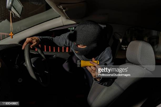 a thief dressed in black with balaclava on his head is trying to steal the car from the city streets - looting stock pictures, royalty-free photos & images