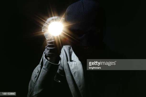 thief holding a torch in dark - burglar stock pictures, royalty-free photos & images