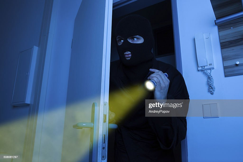 Thief Holding Flashlight While Entering Into House : Stock Photo