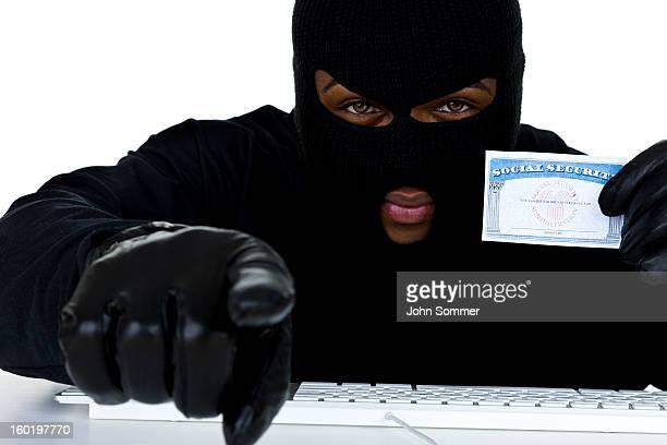 Ladrón sosteniendo la tarjeta de estar y en el ordenador