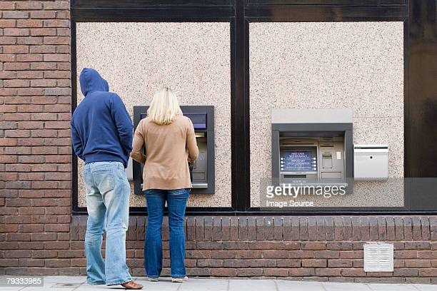 thief looking over womans shoulder at cash machine - looking over shoulder ストックフォトと画像