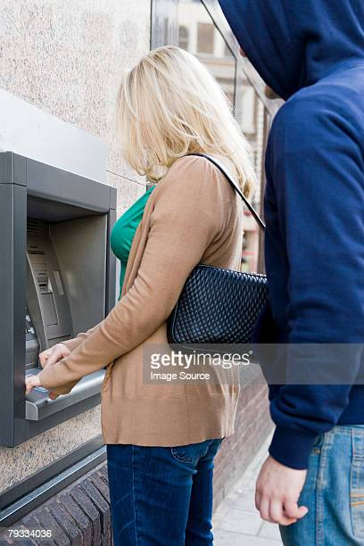 Thief looking over womans shoulder at cash machine