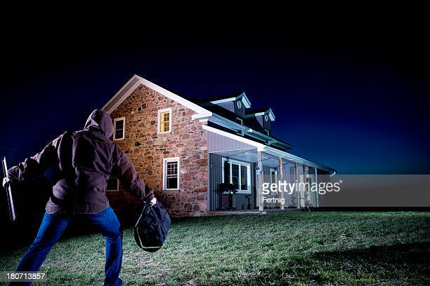 Thief outside a house at night