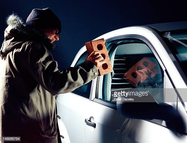 Thief putting a brick through a car window