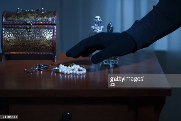 thief reaching for a string of pearls - stealing stock pictures, royalty-free photos & images