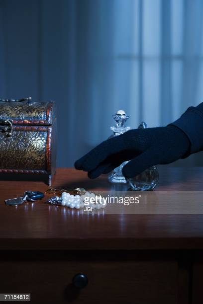 Thief reaching for a string of pearls