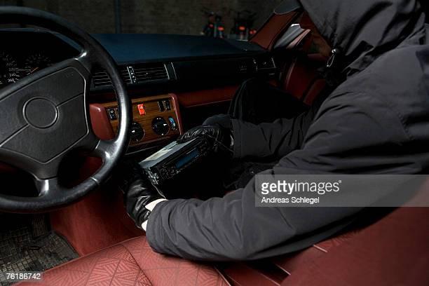 A thief stealing a car stereo