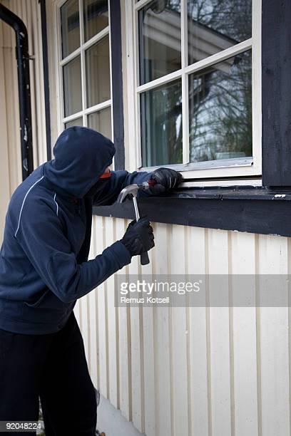 Thief trying to break open a window w/ hammer & screwdriver