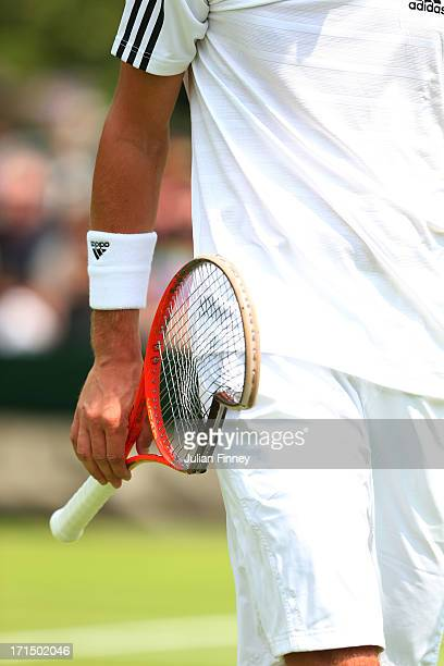 Thiemo De Bakker of Netherlands carries his broken racquet back to his seat during his Gentlemen's Singles first round match against James Blake of...