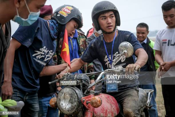 Thien 16yearsold Minsk motorcyclist gets advices from his friends during the offroad race on November 5 2017 in Hanoi Vietnam A new generation of...