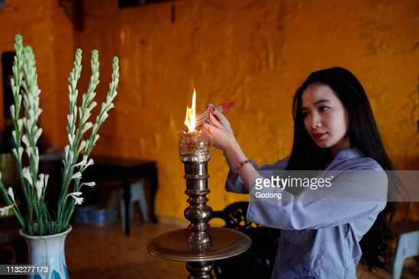 Thien Hung buddhist temple Praying woman with incense sticks in hands Ho Chi Minh City Vietnam