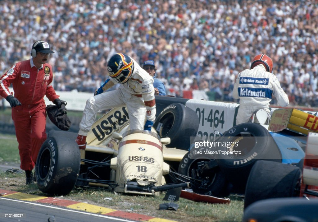 Thierry Boutsen of Belgium exits his #18 Barclay Arrows BMW Arrows A8 following an accident during the 62nd lap of the British Grand Prix at Brands Hatch, England on 13th July 1986. Italian racing driver Piercarlo Ghinzani is pictured on right standing next to his crashed #21 Osella Squadra Corse Osella FA1H car.