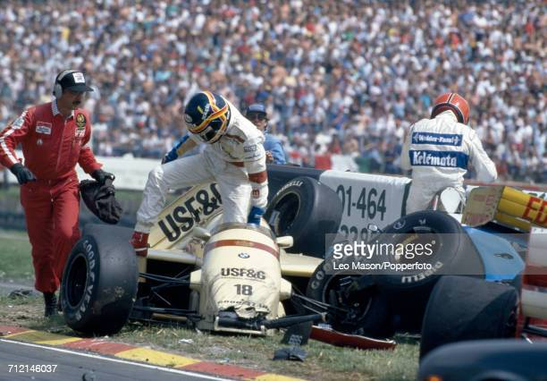 Thierry Boutsen of Belgium exits his Barclay Arrows BMW Arrows A8 following an accident during the 62nd lap of the British Grand Prix at Brands Hatch...
