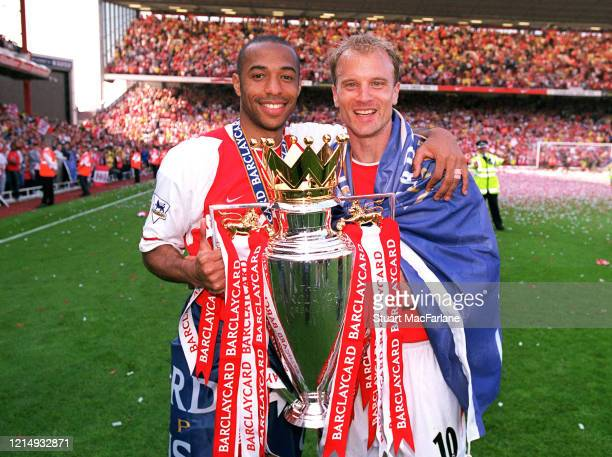 Thierry Henry and Dennis Bergkamp of Arsenal with the Premier League Trophy after the Premier League match between Arsenal and Leicester City on May...