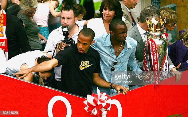 Thierry Henry and Patrick Vieira are seen at the front of the bus outside the Islington Town Hall during the Arsenal Football Club victory parade to...