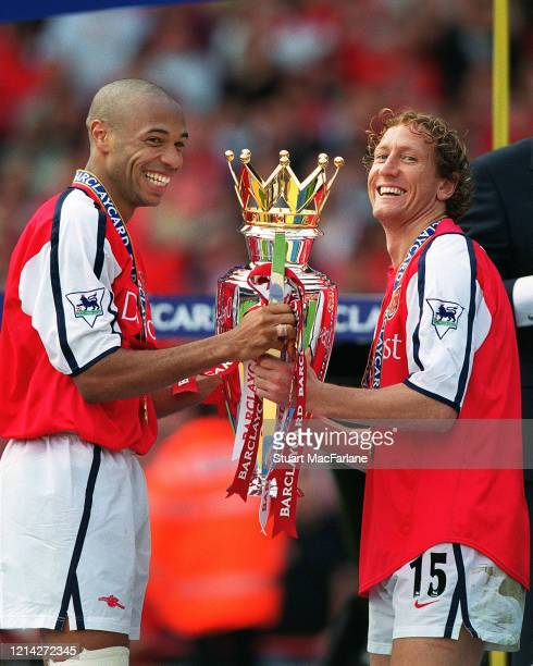Thierry Henry and Ray Parlour of Arsenal with the Premier League Trophy after the Premier League match between Arsenal and Everton on May 11, 2002 in...
