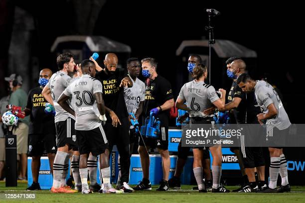 Thierry Henry head coach and Romell Quioto of Montreal Impact speak during a water break in the second half of the MLS is Back Tournament at ESPN...