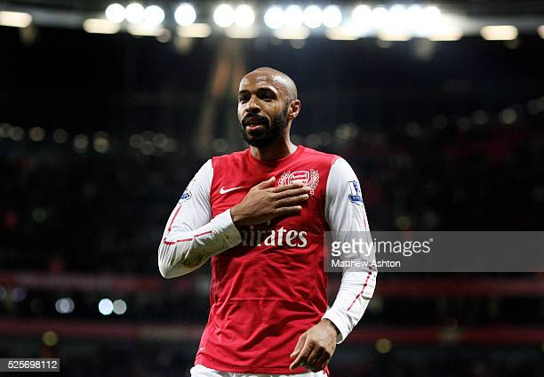 Thierry Henry of Arsenal celebrates scoring the winning goal at the end of the match by patting the Arsenal badge on his shirt