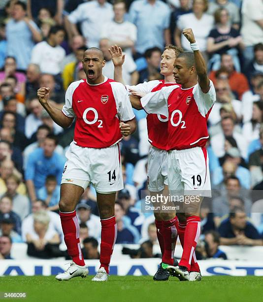 Thierry Henry of Arsenal celebrates with teammates Gilberto and Ray Parlour after the first goal during the FA Barclaycard Premiership match between...