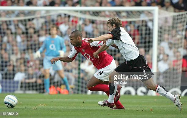 Thierry Henry of Arsenal gets tackled by Moritz Volz of Fulham during the Barclays Premiership match between Fulham and Arsenal at Craven Cottage on...