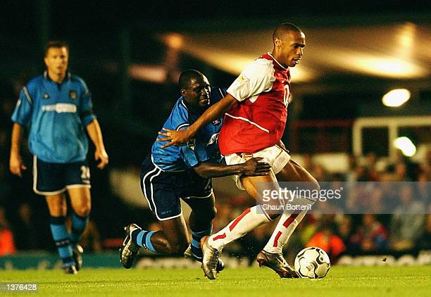 Thierry Henry of Arsenal is challenged to the ball by MarcVivien Foe of Manchester City during the FA Barclaycard Premiership match between Arsenal...