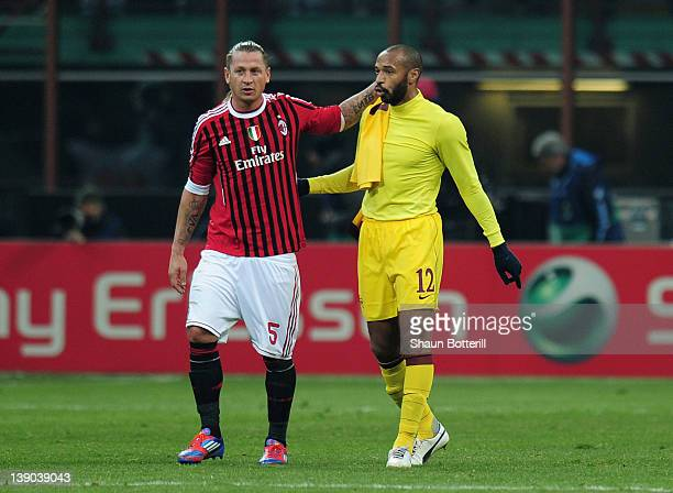 Thierry Henry of Arsenal is consoled by Philippe Mexes of AC Milan after the UEFA Champions League round of 16 first leg match between AC Milan and...