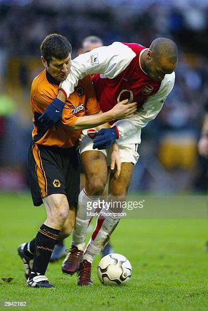 Thierry Henry of Arsenal is held by Denis Irwin of Wolves in a tackle during the FA Barclaycard Premiership match between Wolverhampton Wanderers and...