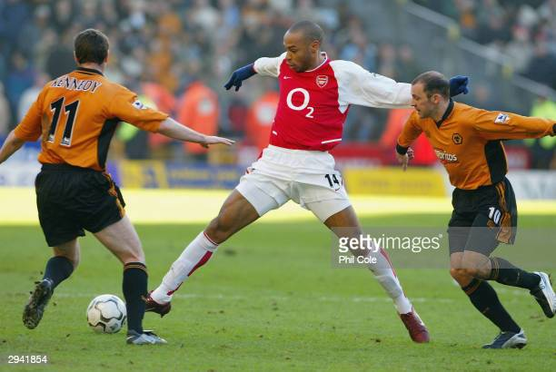 Thierry Henry of Arsenal is tackled by Colin Cameron and Mark Kennedy of Wolves during the FA Barclaycard Premiership match between Wolverhampton...