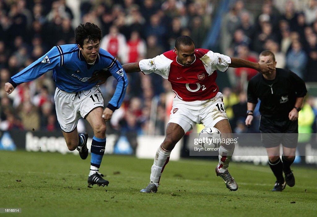Thierry Henry of Arsenal and Sun Jihai of Manchester City : Nachrichtenfoto