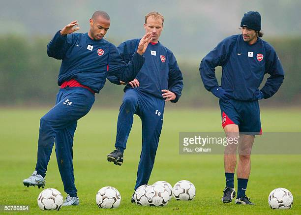 Thierry Henry of Arsenal shows off his skills to Dennis Bergkamp and Robert Pires during the Arsenal Football Club training session at London Colney...