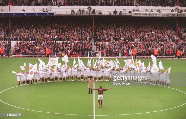 Thierry Henry of Arsenal walks to the centre circle to be greeted by former Arsenal player Ian Wright who was there to present him with a golden...