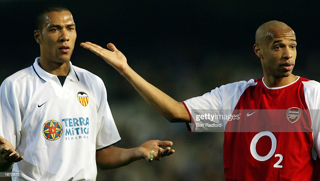 Thierry Henry of Arsenal with John Carew of Valencia show they are the same colour to try to calm the fans down after Thierry Henry gets racial abuse from the home fans : Foto di attualità